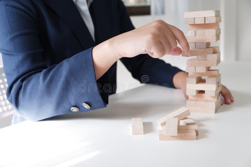 Primo piano delle donne che giocano il gioco della pila dei blocchi di legno, concetto di crescita di affari, glambling, rischio fotografia stock