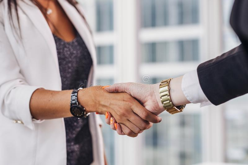 Primo piano delle donne di affari che stringono le mani che si accolgono prima della riunione immagine stock libera da diritti