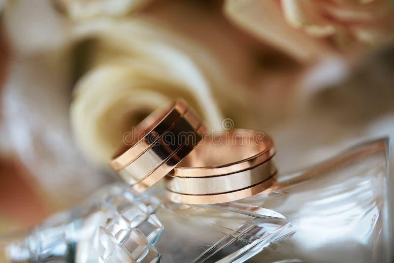 Primo piano delle fedi nuziali su fondo delle rose e del vetro, accessori di nozze fotografie stock