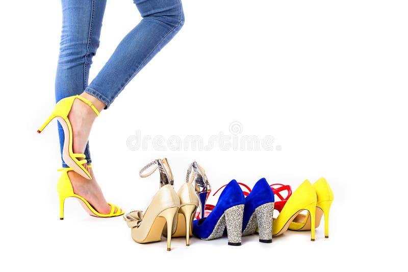 Primo piano delle gambe della donna accanto a molte scarpe variopinte contro backgorund bianco fotografie stock libere da diritti