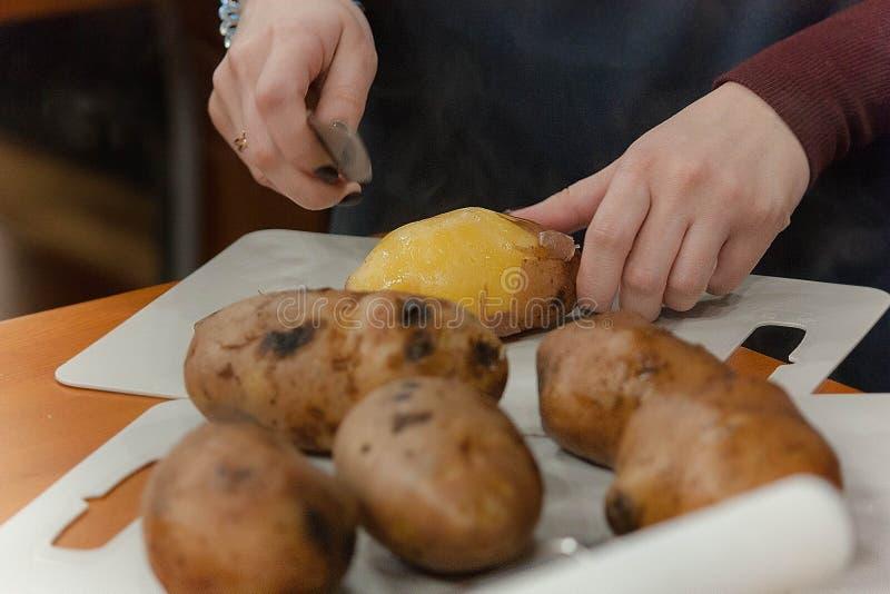Primo piano delle mani che puliscono le patate immagine stock