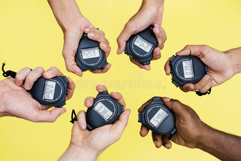 Primo piano delle mani che tengono gli orologi di arresto con fondo giallo fotografie stock libere da diritti