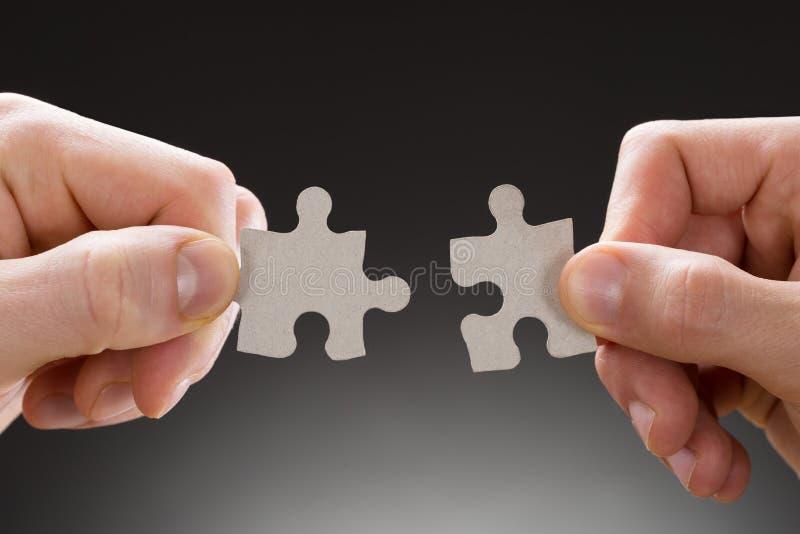 Primo piano delle mani che tengono i pezzi del puzzle immagine stock