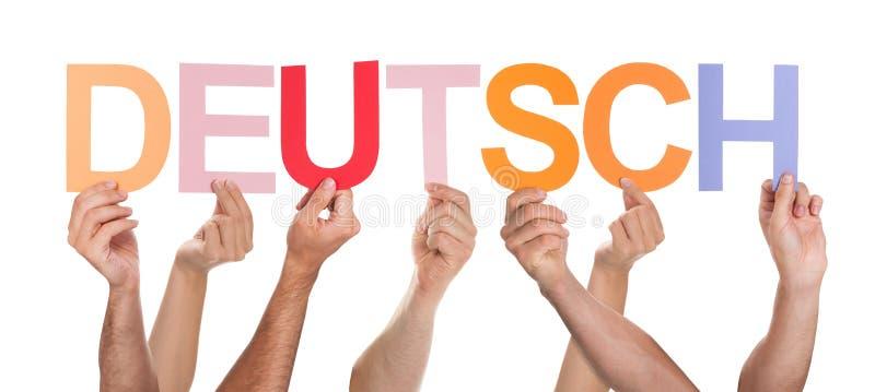 Primo piano delle mani che tengono testo Deutsch immagine stock libera da diritti