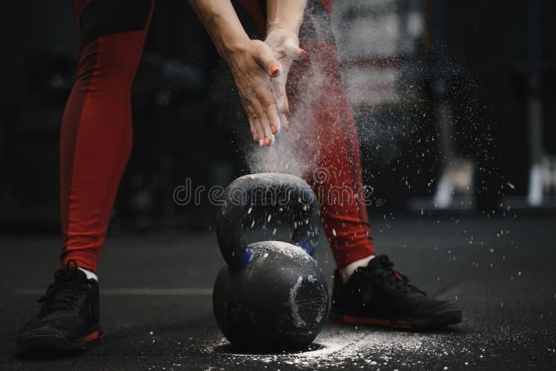 Primo piano delle mani claping dell'atleta femminile del crossfit con la nuvola di polvere mentre protezione della magnesia fotografie stock libere da diritti