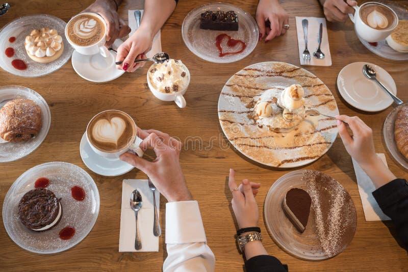 Primo piano delle mani con i dessert e le tazze di caff? in un caff? fotografie stock