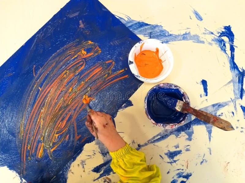 Primo piano delle mani dei bambini che dipingono durante l'attività di scuola - imparando facendo, dall'istruzione e dall'arte, c immagine stock libera da diritti