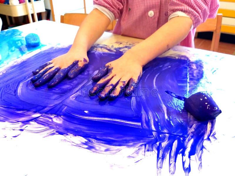 Primo piano delle mani dei bambini che dipingono durante l'attività di scuola - pittura del ghiaccio - che impara facendo, dall'i fotografie stock libere da diritti