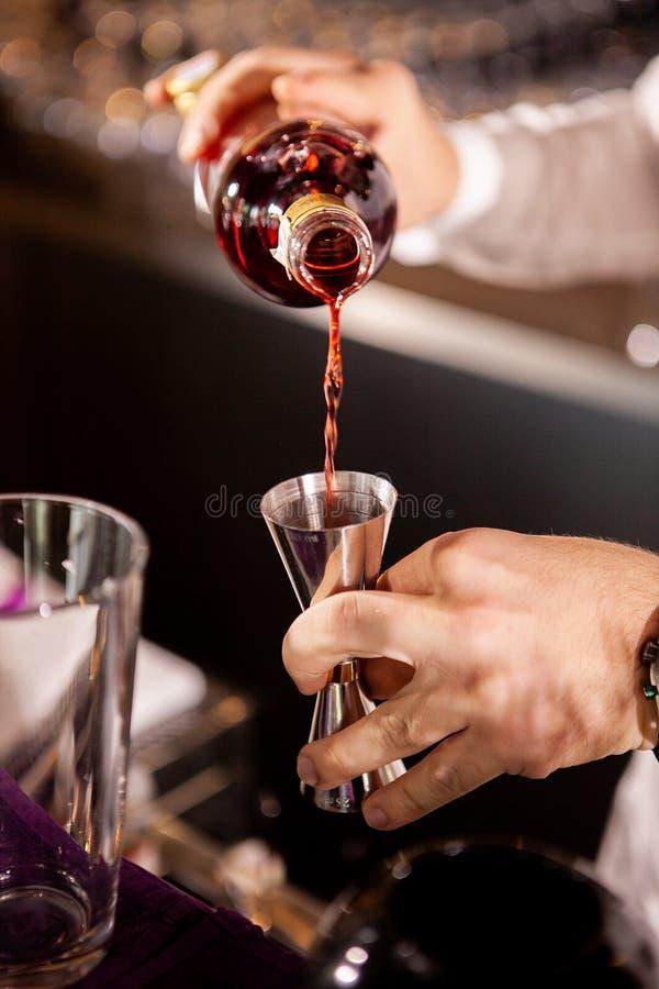 Primo piano delle mani del barista che versano bevanda alcolica fotografia stock libera da diritti