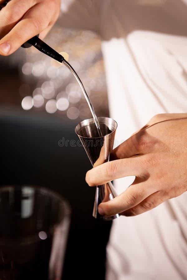 Primo piano delle mani del barista che versano bevanda alcolica immagini stock libere da diritti