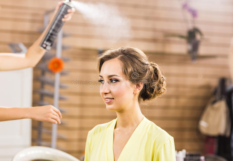 Primo piano delle mani del parrucchiere facendo uso della lacca sui capelli del cliente al salone fotografia stock