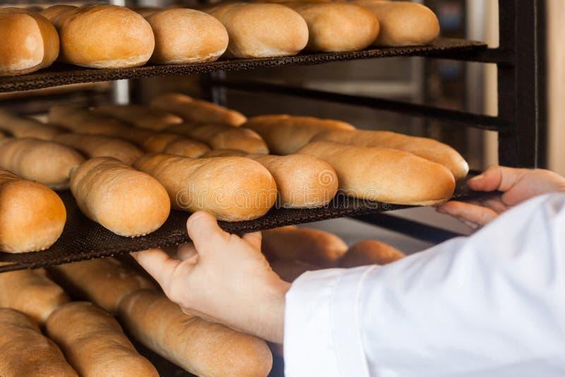 Primo piano delle mani dell'uomo professionale del cuoco unico nella condizione uniforme bianca vicino agli scaffali pieni con pa immagini stock