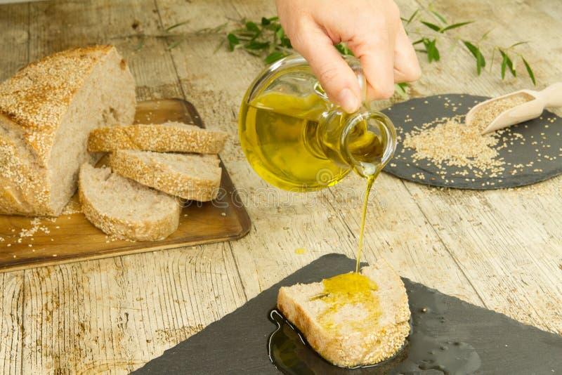 Primo piano delle mani della donna che versano olio d'oliva vergine extra da un'ampolla su una fetta di pane casalingo in composi immagine stock