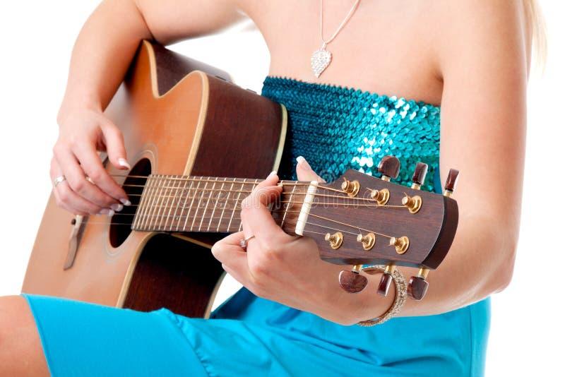 Primo piano delle mani della donna con la chitarra acustica fotografia stock
