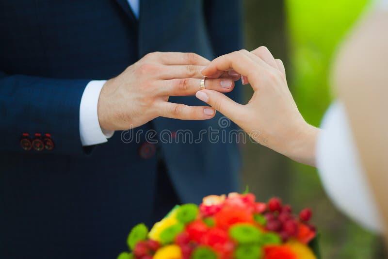 Primo piano delle mani delle coppie irriconoscibili nuziali con le fedi nuziali la sposa tiene il mazzo di nozze dei fiori fotografia stock