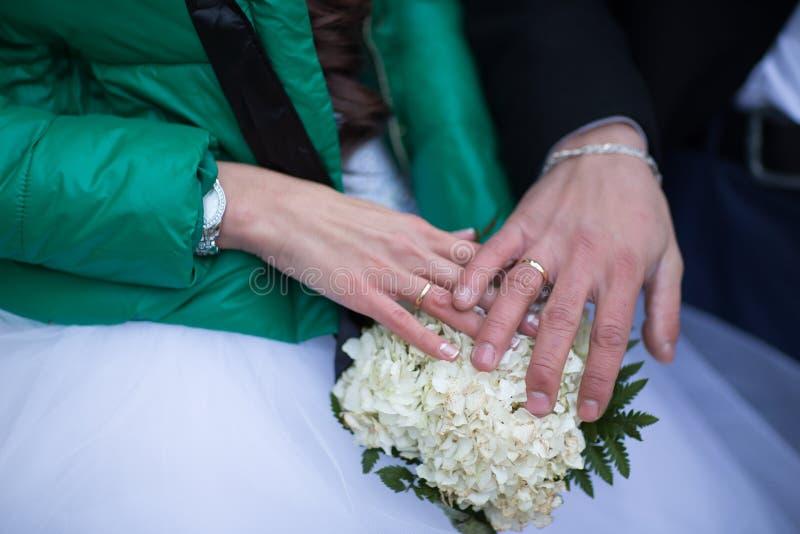 Primo piano delle mani delle coppie nuziali con le fedi nuziali immagine stock