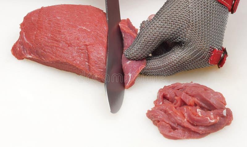 Primo piano delle mani delle fette di un taglio del macellaio di carne cruda fuori da un grande lombo immagine stock