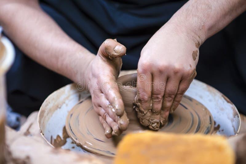 Primo piano delle mani di funzionamento maschio del vasaio con Clay Lump del tornio da vasaio sul gruppo di lavoro dentro immagine stock