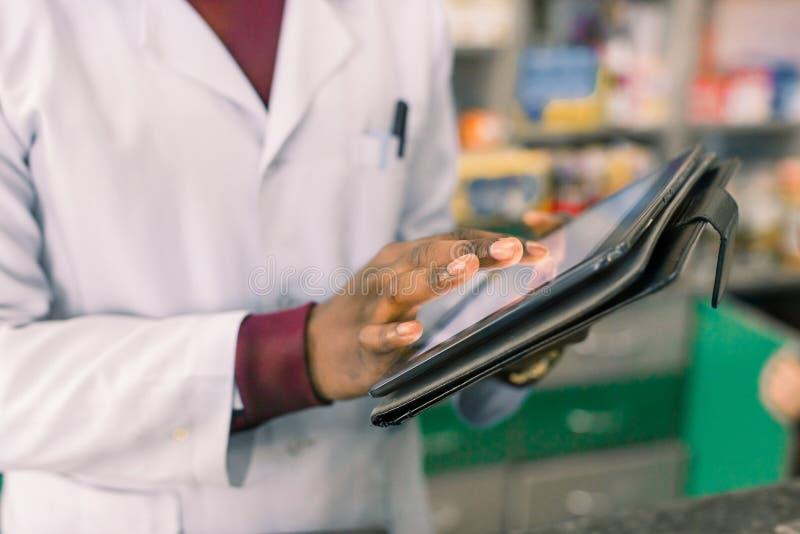Primo piano delle mani di medico afroamericano o del farmacista dell'uomo che utilizza compressa digitale mentre stando nell'inte immagine stock