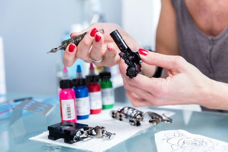 Primo piano delle mani di un artista femminile che prepara una macchina professionale del tatuaggio fotografia stock