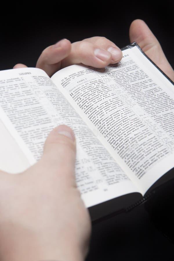 Primo piano delle mani di una bibbia della holding dell'uomo immagini stock libere da diritti