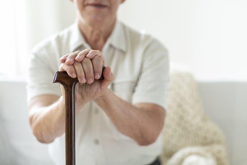 Primo piano delle mani di una tenuta anziana dell'uomo su una canna immagini stock