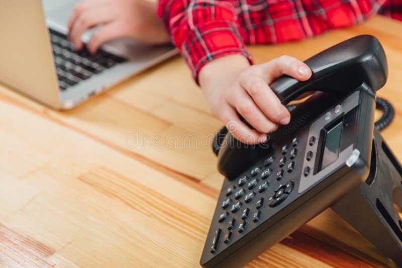 Primo piano delle mani delle donne in un ufficio con un telefono in loro mani che si trovano sulla tavola, posto di lavoro Contro fotografie stock