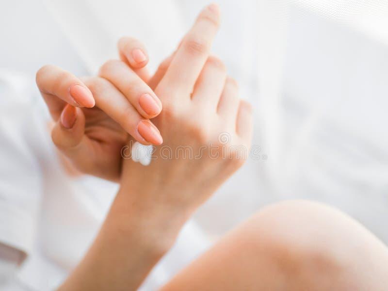 Primo piano delle mani femminili che applicano crema per le mani fotografie stock