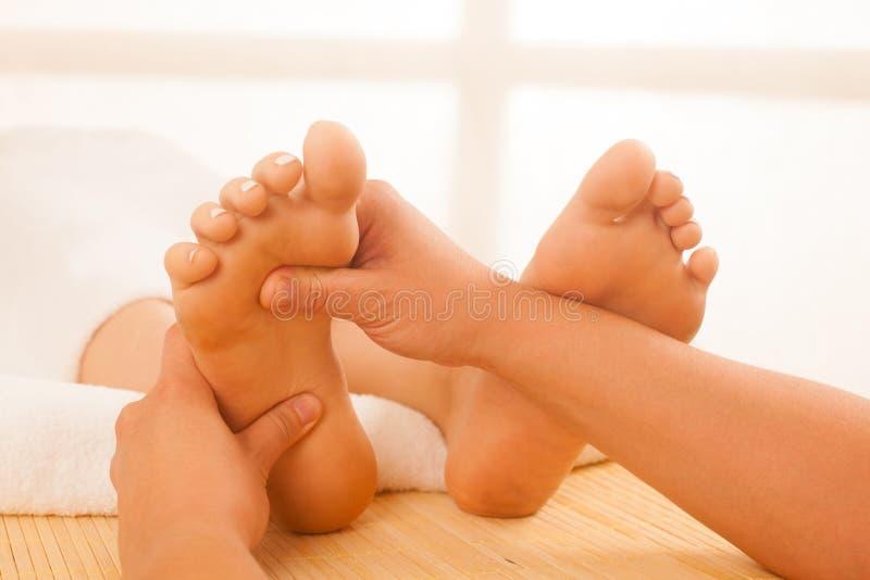 Primo piano delle mani femminili che fanno massaggio del piede immagine stock