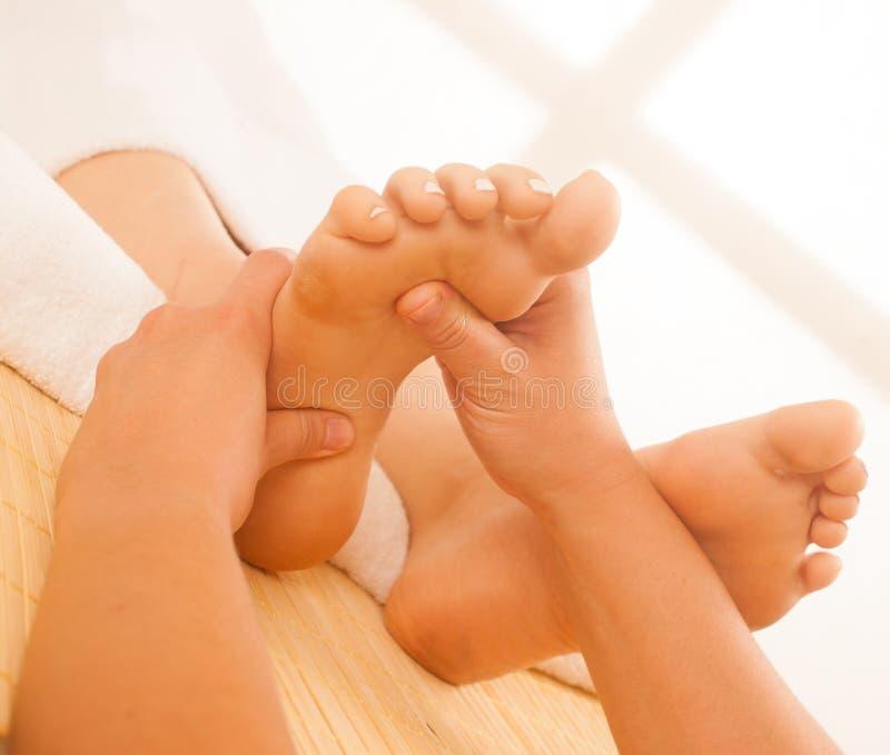 Primo piano delle mani femminili che fanno massaggio del piede fotografia stock