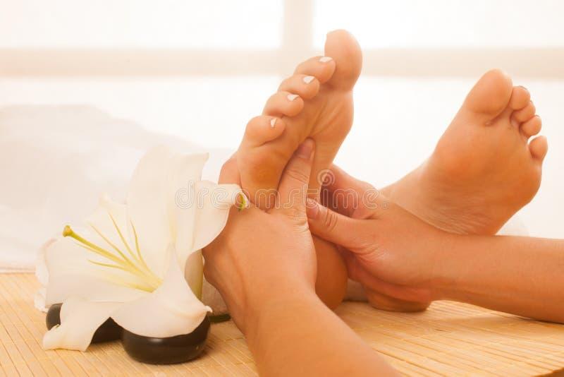 Primo piano delle mani femminili che fanno massaggio del piede immagini stock
