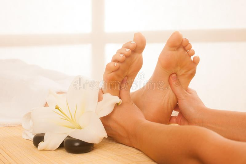 Primo piano delle mani femminili che fanno massaggio del piede fotografie stock libere da diritti