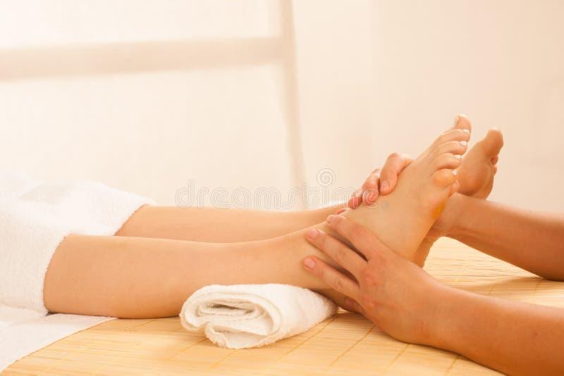 Primo piano delle mani femminili che fanno massaggio del piede fotografie stock