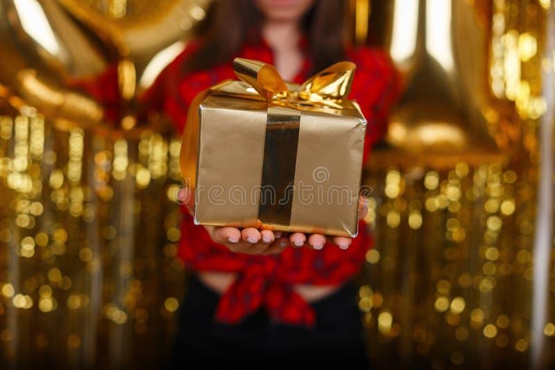 Primo piano delle mani femminili che tengono un nastro dell'oro avvolto regalo Piccolo regalo nelle mani di una donna dell'intern immagini stock libere da diritti