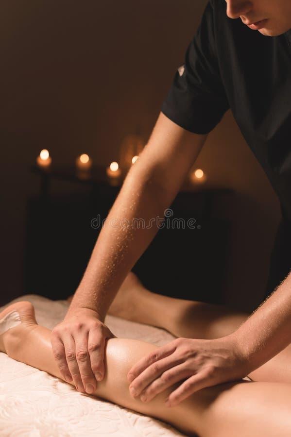 Primo piano delle mani maschii che fanno massaggio del vitello delle gambe femminili in una stanza scura con le candele nei prece fotografie stock