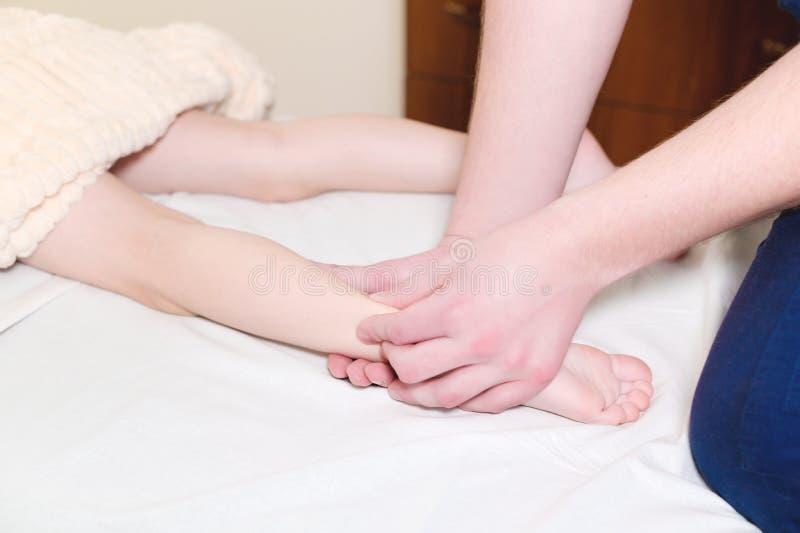 Primo piano delle mani maschii del chiropratico che massaggiano i vitelli di piccolo paziente Un ragazzino alla ricezione della p immagine stock libera da diritti