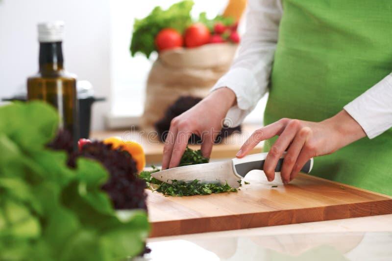 Primo piano delle mani umane che cucinano l'insalata delle verdure in cucina sulla tavola di vetro con la riflessione fotografie stock