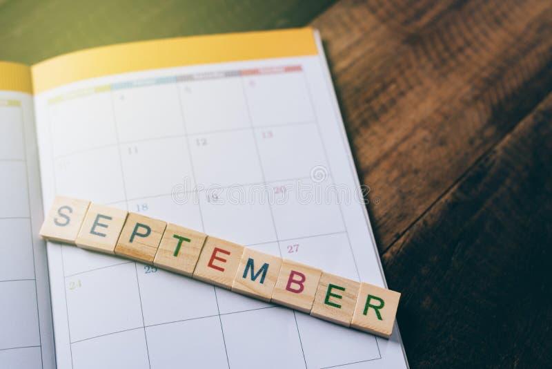 Primo piano delle mattonelle di alfabeto di SETTEMBRE sul calendario del libro del pianificatore sulla tavola di legno immagini stock libere da diritti