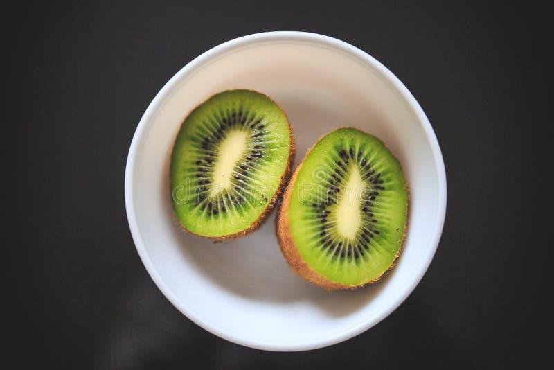 Primo piano delle metà del kiwi nella ciotola con colore verde esotico e fondo nero fotografia stock