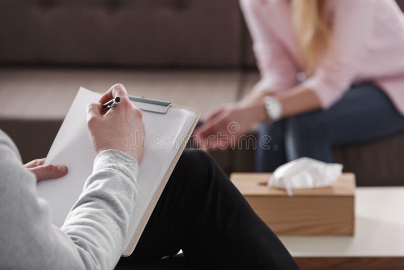 Primo piano delle note di scrittura della mano del terapista durante ses di consiglio fotografia stock libera da diritti