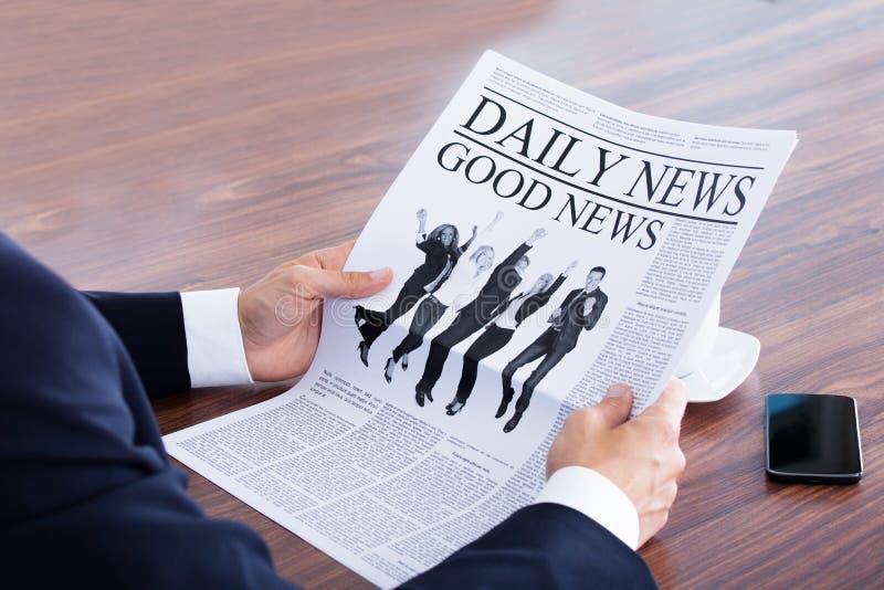 Primo piano delle notizie della lettura dell'uomo d'affari immagini stock libere da diritti