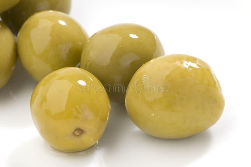 Primo piano delle olive verdi su un bianco immagini stock