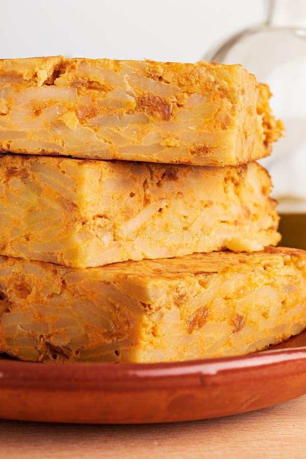 Primo piano delle porzioni di omelette spagnola casalinga della patata con gli ingredienti naturali immagini stock
