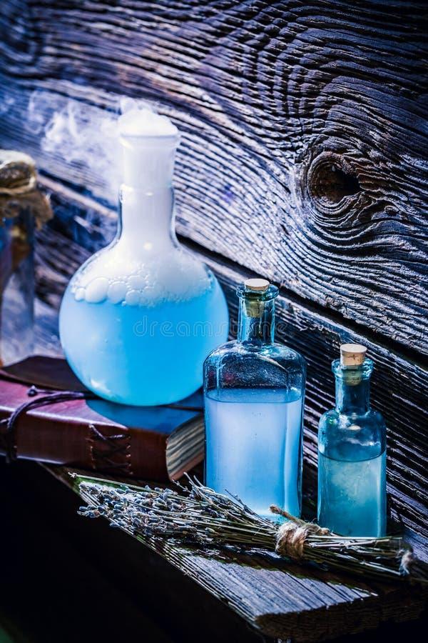 Primo piano delle pozioni blu magiche in cottage della strega per Halloween fotografie stock libere da diritti