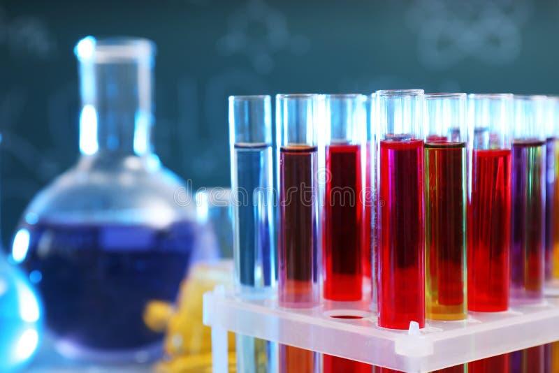 Primo piano delle provette in scaffale contro fondo vago Cristalleria di chimica immagine stock libera da diritti