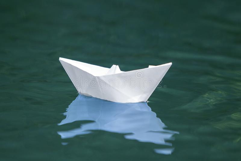 Primo piano delle quiete di galleggiamento della piccola barca di carta bianca semplice di origami immagini stock libere da diritti