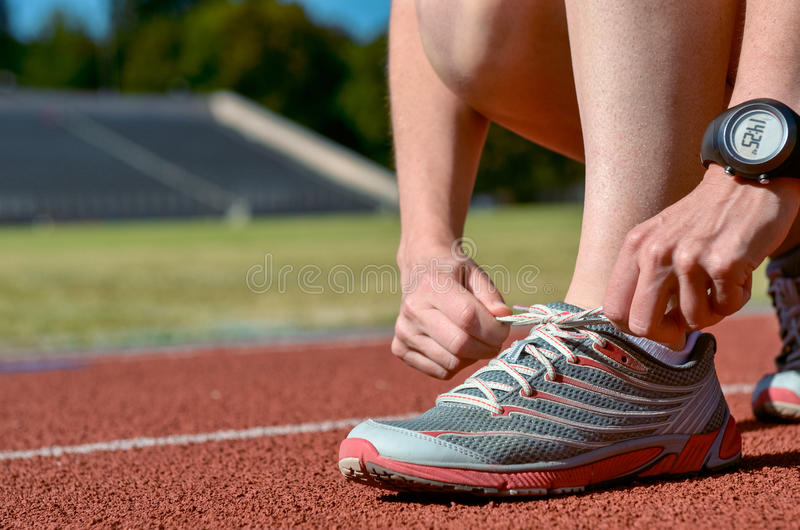 Primo piano delle scarpe da corsa, atleta femminile del corridore che lega i pizzi per la formazione e pareggiare sulla pista del fotografie stock libere da diritti