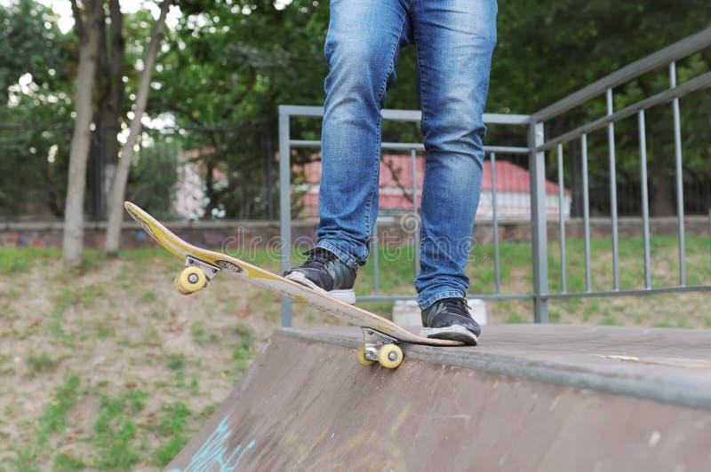 Primo piano delle scarpe da tennis del piede e dei jeans di un skateboarder prima della corsa immagine stock