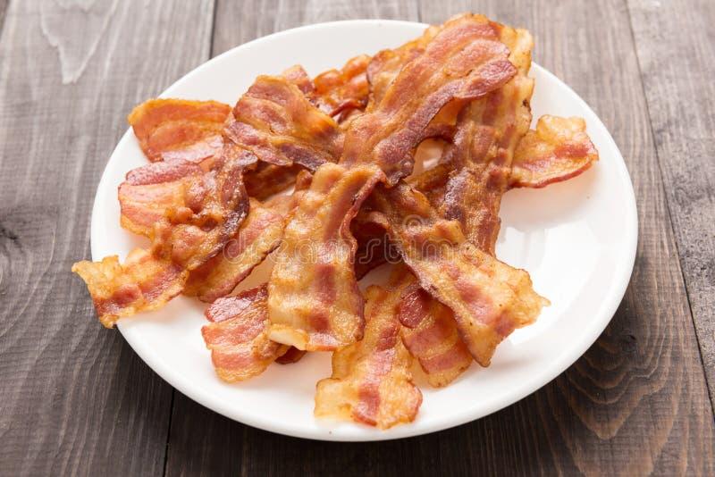 Primo piano delle strisce di bacon fritte sul piatto bianco immagine stock