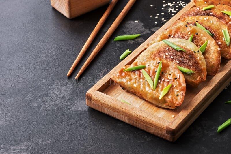 Primo piano dello gnocco fritto asiatico casalingo su fondo di pietra nero Fuoco selettivo, posto per testo fotografia stock